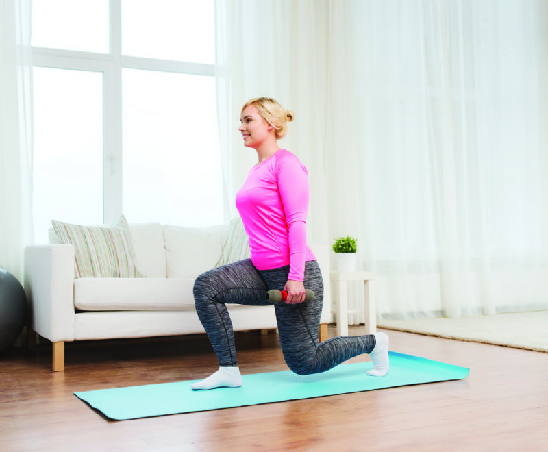 Young woman doing home workout fitness in living room lounge