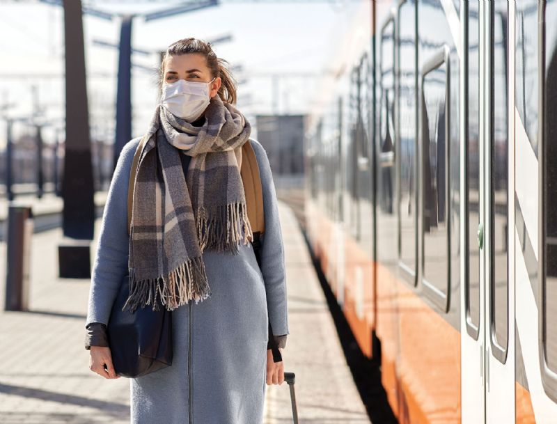 Woman wearing face mask in public train station