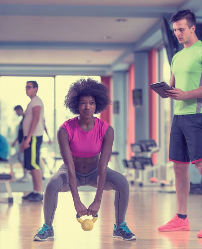 Woman at gym with male personal trainer exercise