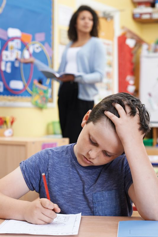 Young boy frustrated doing work at school dyslexia