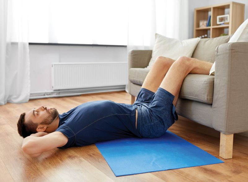 Man doing core exercises in living room