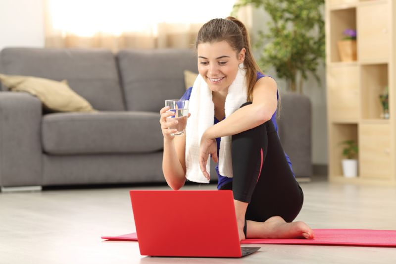 Woman doing online workout fitness class from home