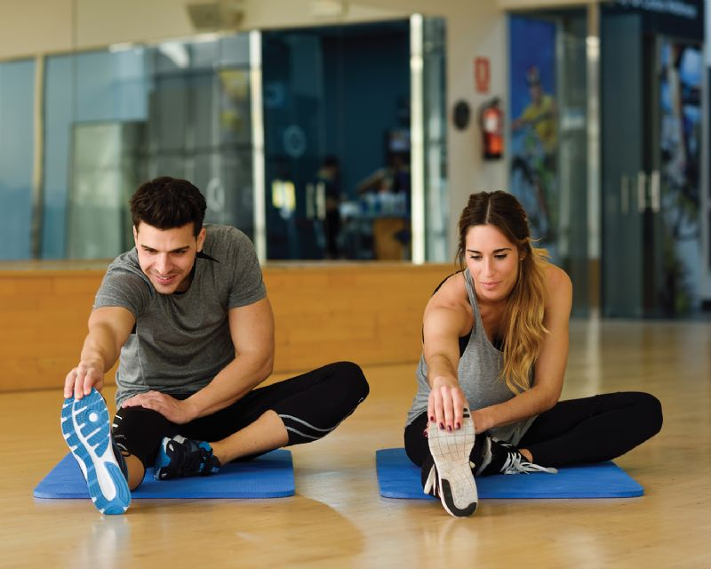 Man and woman stretching in the gym