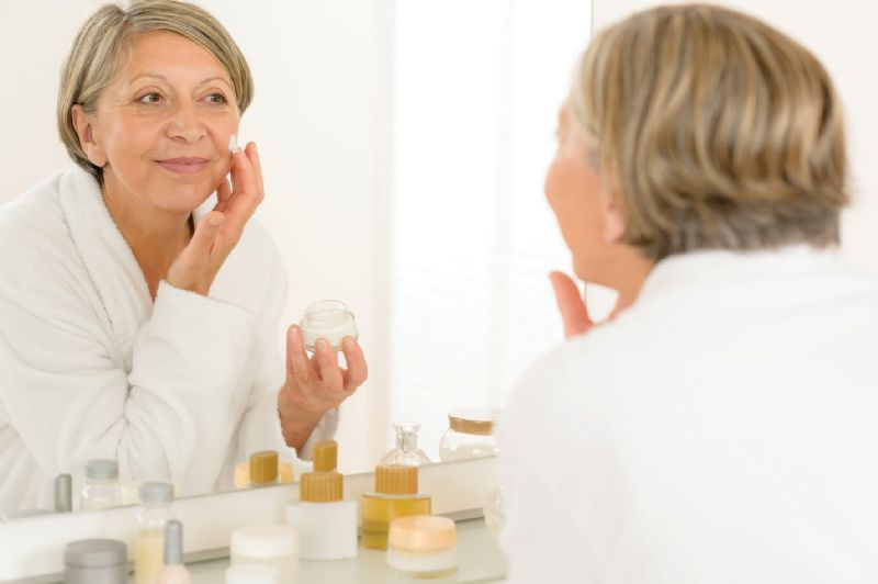 Senior woman putting on face cream mirror bathroom