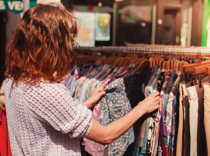Young woman shopping second-hand clothes rail