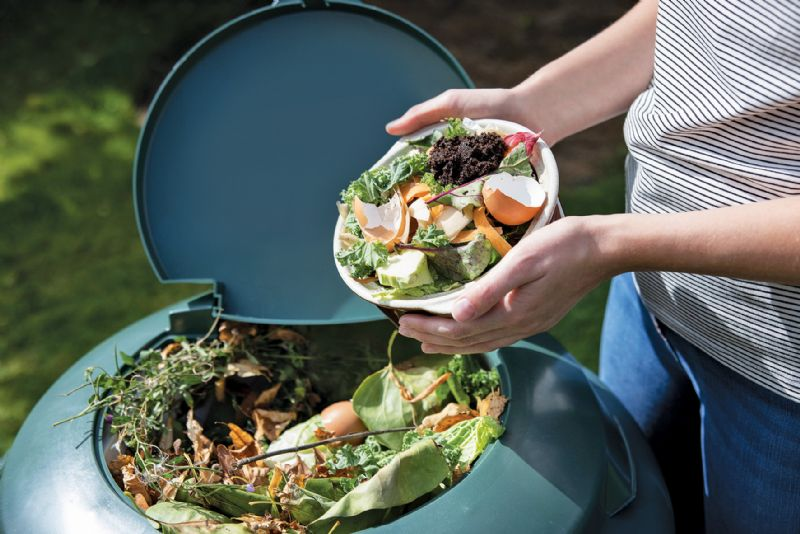 Woman putting food in compost bin garden